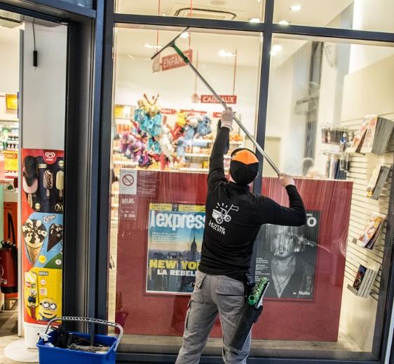 David le laveur de vitres nettoie les vitres d'une boutique en hauteur à la perche télescopique