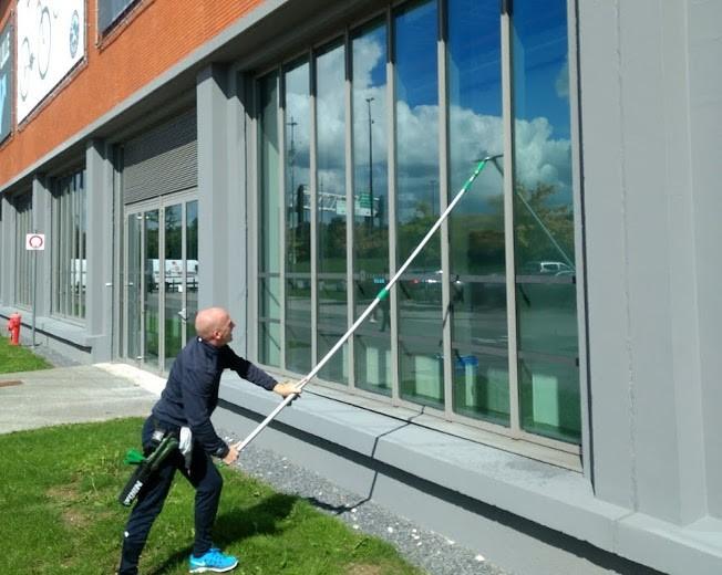 David le laveur de vitres nettoie les grandes baies vitrés d'une salle de sport à la perche télescopique